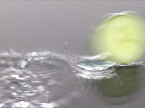 Fresh cucumber slices roll across a wet surface Stock Video Footage