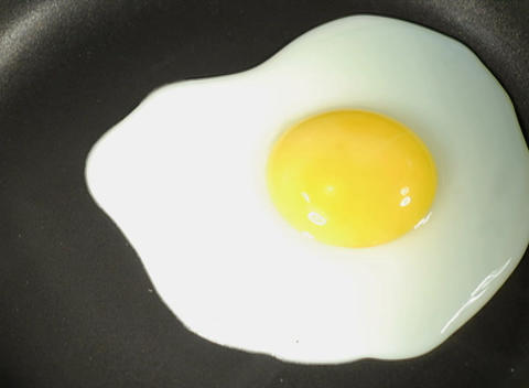 A raw egg is cooked in a skillet Stock Video Footage