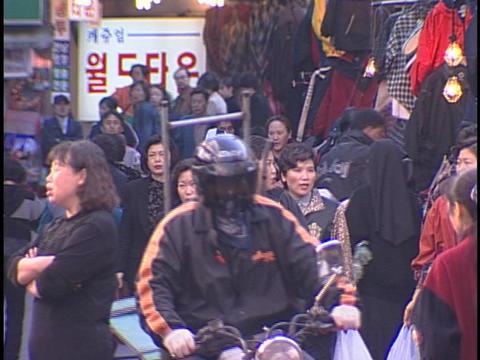 Pedestrians walk and talk on a crowded city sidewalk Stock Video Footage