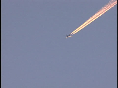An airplane streaks across the sky Live Action