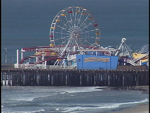 A ferries wheel spins at a carnival on a boardwalk Stock Video Footage