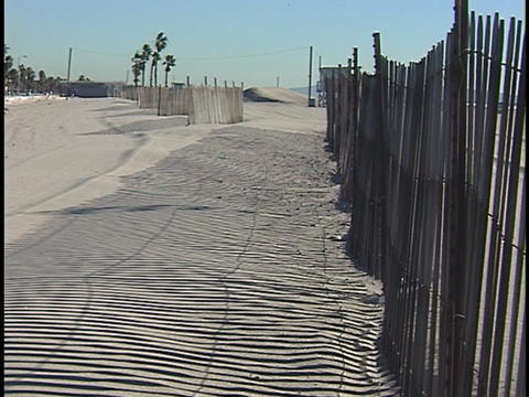 A fence casts shadows onto a bare sandy beach Footage