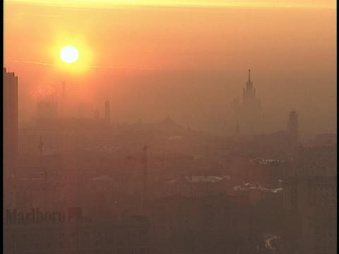 The sun radiates through thick smog above a city Footage
