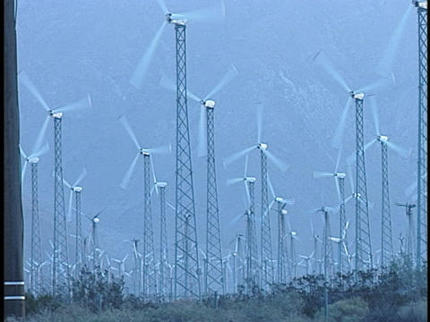A field of enormous wind turbines turn rapidly in the wind Stock Video Footage