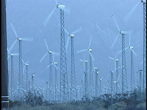 A Field Of Enormous Wind Turbines Turn Rapidly In The Wind stock footage