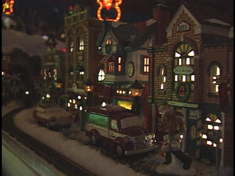 A model train speeds on its tracks around a Christmas figurine city Footage