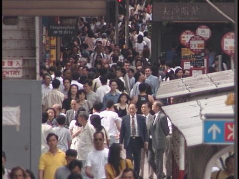Pedestrians walk on a crowded sidewalk Stock Video Footage