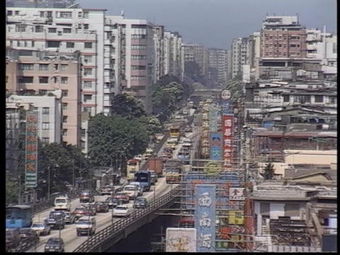 Traffic drives down a busy city street Stock Video Footage
