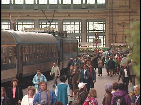 Crowds of people walk on a train-station platform Stock Video Footage