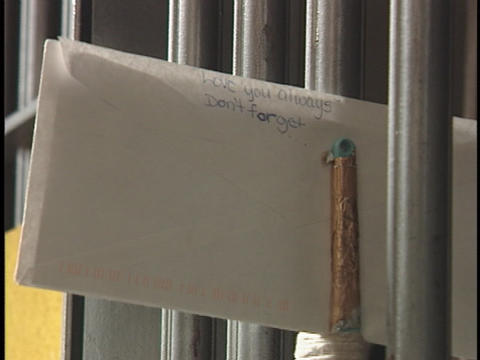 A prisoner places a letter between the bars on his... Stock Video Footage