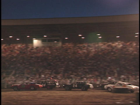 Demolition cars race around tires in an outdoor arena Stock Video Footage