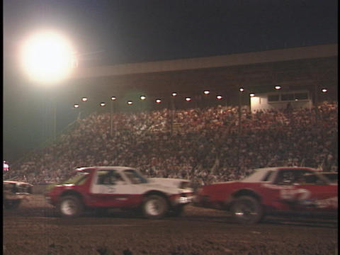 Cars in a demolition derby pass by the crowd Live Action