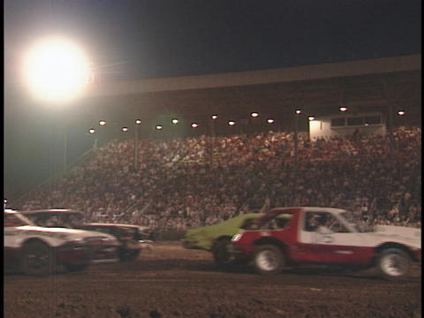 Cars in a demolition derby pass by the crowd Stock Video Footage