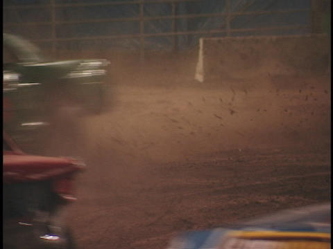 Cars race around the dirt track at a demolition derby Footage