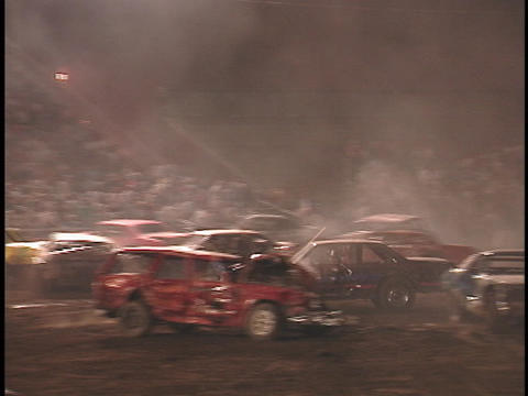 A demolition car drives across the arena in reverse and crashes into a car on the other side Footage