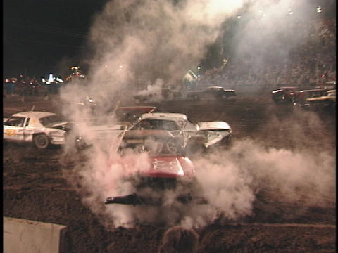 A demolition car with a smoking hood reverses to get back into the action Footage