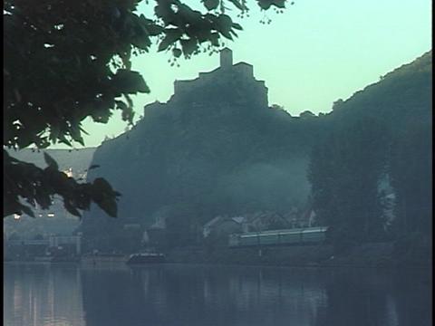 A train speeds across a track near a hazy bay Stock Video Footage