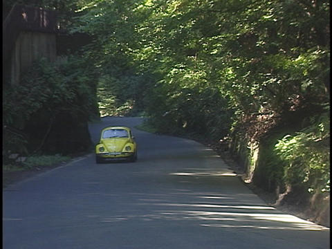 A yellow Volkswagen Bug drives on a country road Stock Video Footage