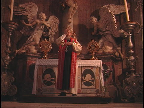 A catholic priest says a prayer in a church Live Action