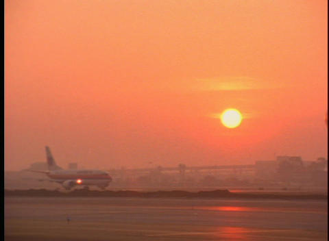 Passenger planes taxi on the runway during golden hour Stock Video Footage