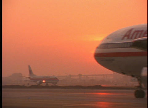 Passenger planes taxi on the runway during golden hour Footage