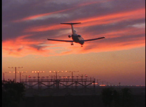 A passenger jet lands on a runway in the golden hour Stock Video Footage