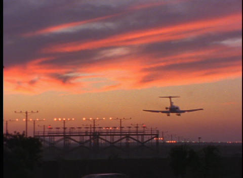 A passenger jet lands on a runway in the golden hour Footage