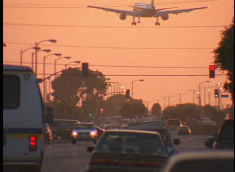 A large airplane flies over a busy city street Footage
