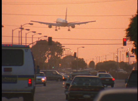 A large airplane flies over a busy city street Stock Video Footage