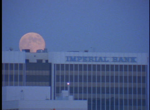 The moon slowly hangs in the sky behind the Imperial Bank Stock Video Footage