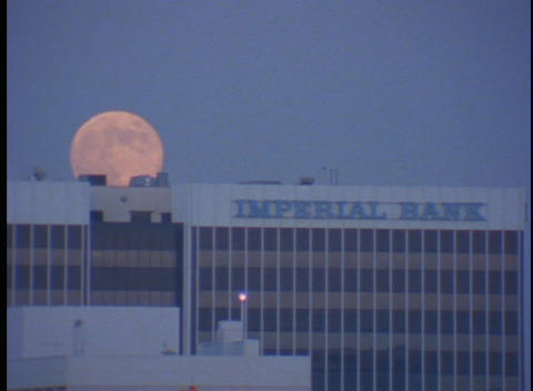 The moon slowly hangs in the sky behind the Imperial Bank Footage