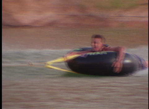 boys skim across the water in inner tubes Stock Video Footage