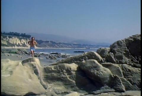A man jogs along a beach Stock Video Footage