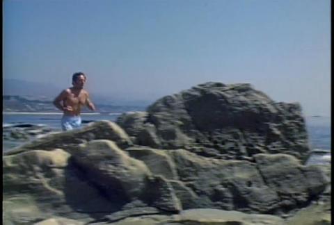 A man jogs along a beach Footage