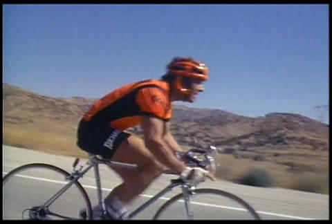 A man on a racing bike pedals along a desert highw Stock Video Footage