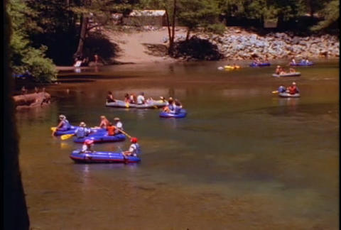 Kids ride innertubes on a river Stock Video Footage