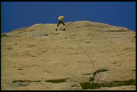 A man rappels down a mountain Footage