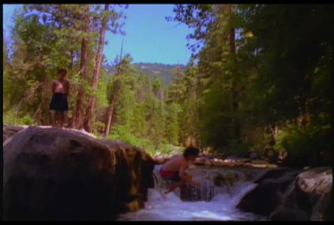 A boy rides a swing and dives into a watering hole Footage