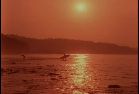 A surfer at sunset Stock Video Footage