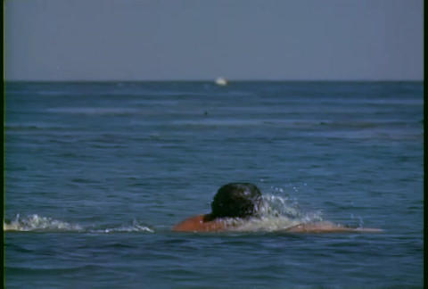 A man swims in the ocean with a fishing boat in th Stock Video Footage