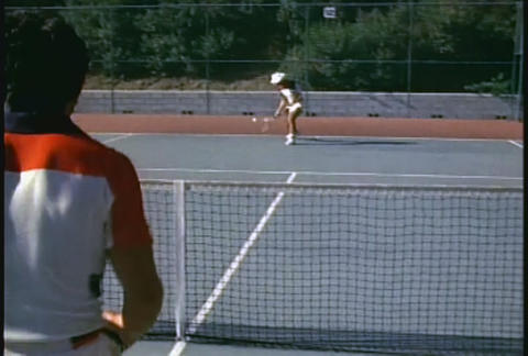 A couple plays tennis in this over the shoulder sh Footage