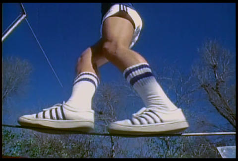 A retro man walks on a tightrope in tennis shoes Stock Video Footage