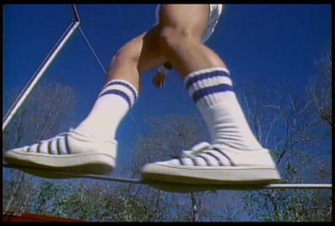 A retro man walks on a tightrope in tennis shoes Footage