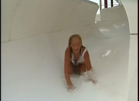 A girl rides a water slide at a water park Stock Video Footage