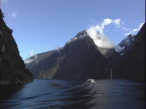 A riverboat travels on a fjord at Milford Sound, New Zealand Stock Video Footage