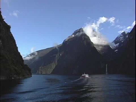 A riverboat travels on a fjord at Milford Sound, New Zealand Footage