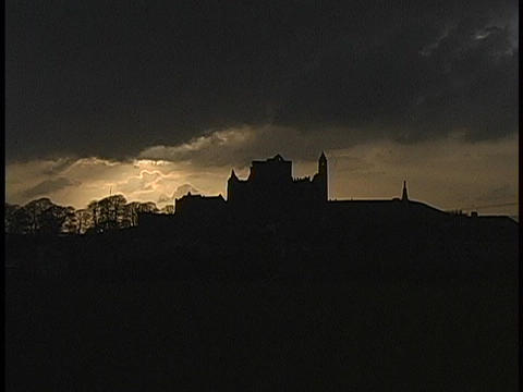 Dark clouds hang over the silhouette of a medieval castle in Europe Footage