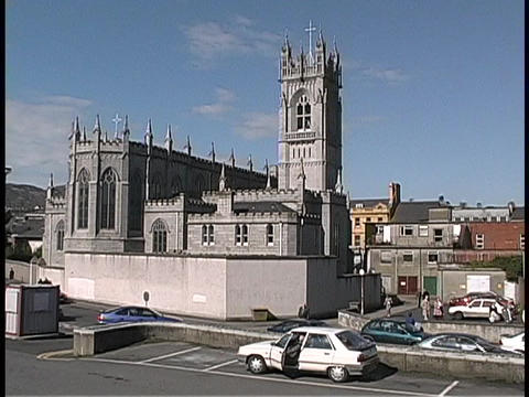 A medieval cathedral is surrounded by traffic in Ireland Footage