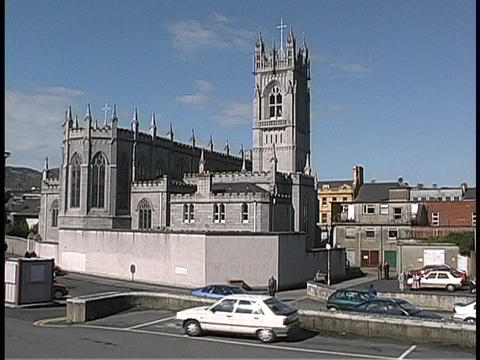 A medieval cathedral is surrounded by traffic in Ireland Stock Video Footage