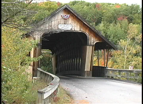 Trees surround an old covered bridge in a peaceful forest in Maine Footage